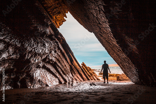Photo A young man exploring the beautiful natural cave that was used in the filming of game of thrones in the flysch of the Itzurun beach in Zumaia