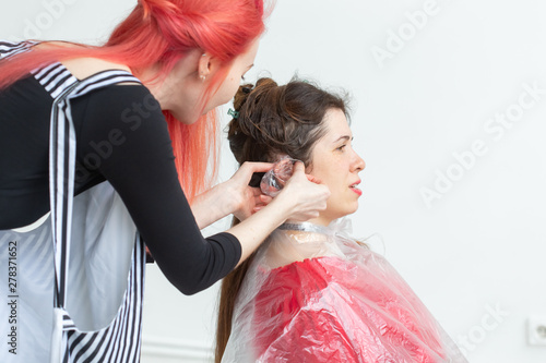 Obraz na plátně  Hair Stylist, beauty and people concept - female hairdresser coloring young woman