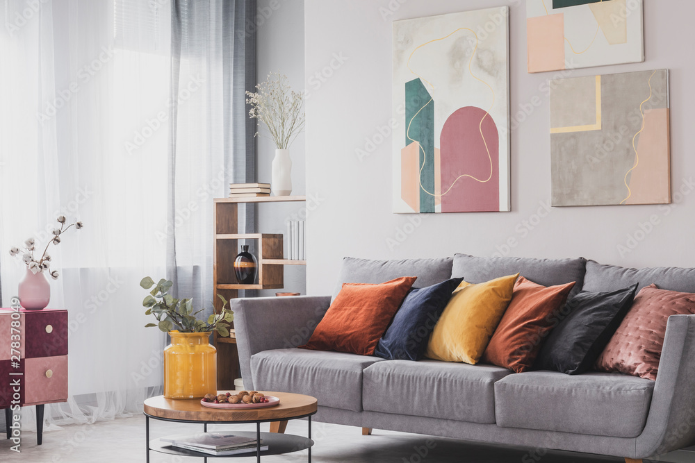 Fototapety, obrazy: Yellow, orange, black and brown pillows on comfortable grey scandinavian sofa in bright living room interior with abstract paintings on the wall