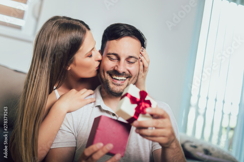 Woman surprising his boyfriend with a gift on the couch at home in the living ro Fototapet