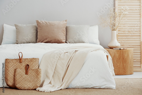 Fotografía White and beige bedding on double bed in simple interior