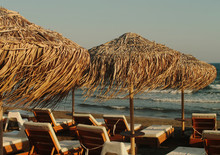 Straw Umbrellas And Sun Beds On A Beach