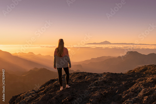 Foto auf Leinwand Dunkelbraun Happy young woman standing and enjoying life at sunset in mountains - gran canaria, spain