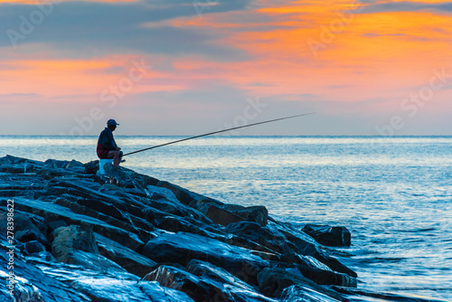 Photo  Angler fishing on the sea shore at sunrise
