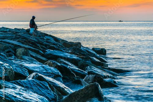 Fotografía Angler fishing on the sea shore at sunrise