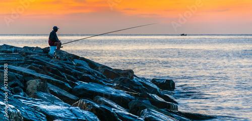 Poster Amsterdam Angler fishing on the sea shore at sunrise