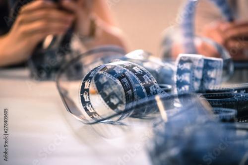 Fotografie, Obraz  Cinema film reel on a cutting table: Filmmaker is working with vintage film stri
