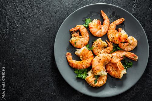 Fotografía  Grilled shrimps on plate on dark background