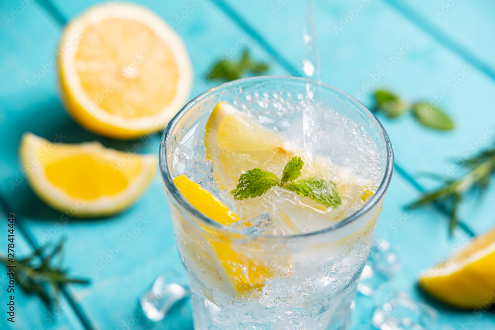 Fototapety, obrazy: Refreshing lemonade in glass with lemon on wooden table