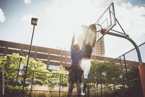 plakat Two street basketball players playing hard on the court