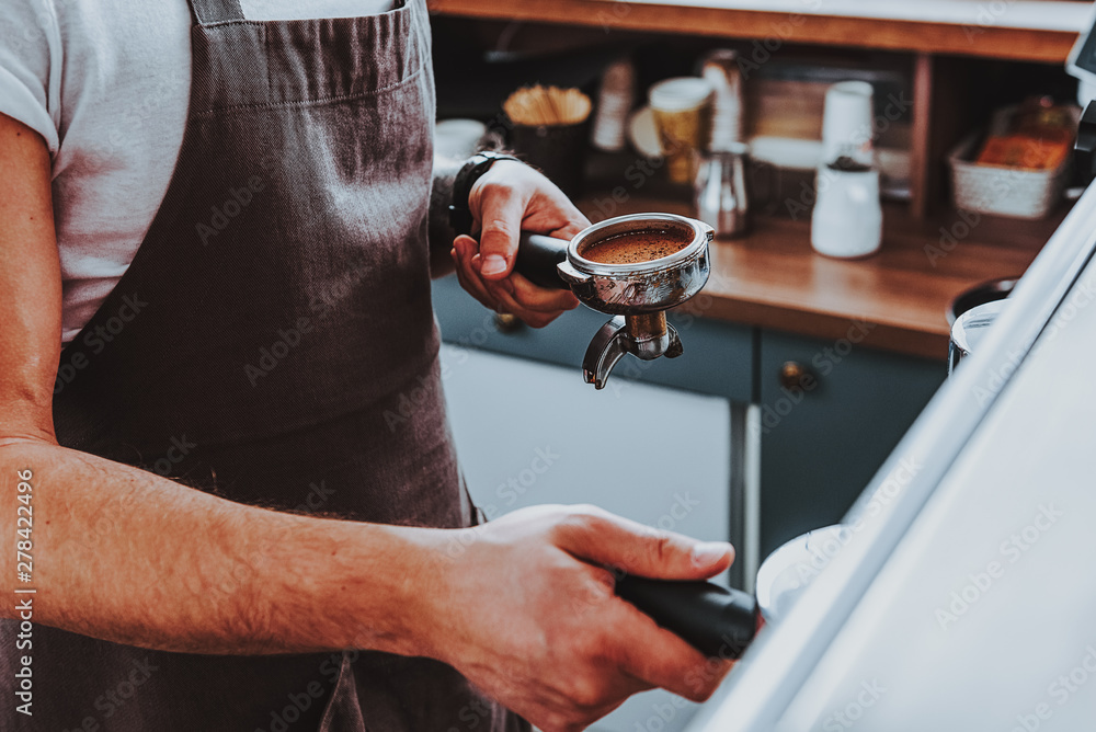 Fototapeta Close up of barista wearing apron holding filter holder