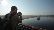 A Man Takes On Camera A Long Barge Floating On A River.