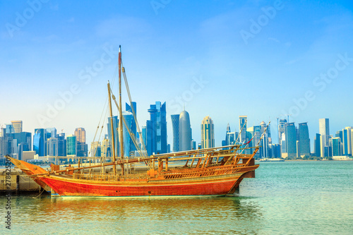 Fényképezés  Traditional wooden dhow in foreground with seafront of Doha Bay and skyscrapers of West Bay skyline on background