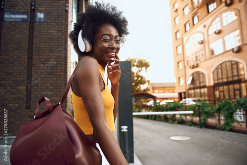 Foto  Happy afro-american lady with bag walking on the street