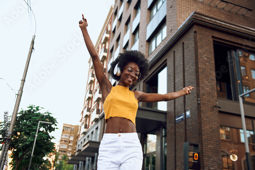 Joyful afro-american lady with dancing in the city - 278428876
