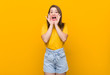 canvas print picture - Young woman teenager wearing a yellow shirt shouting excited to front.