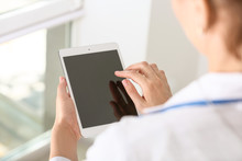 Female Doctor Using Modern Tablet Computer In Clinic, Closeup