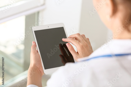 Obraz Female doctor using modern tablet computer in clinic, closeup - fototapety do salonu