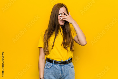 Young ginger redhead woman blink at the camera through fingers, embarrassed covering face.