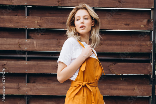 fototapeta na szkło Portrait of an attractive blonde woman poses for the advertisement of a women's clothing store dressed in a light summer white dress on the backyard of a country house