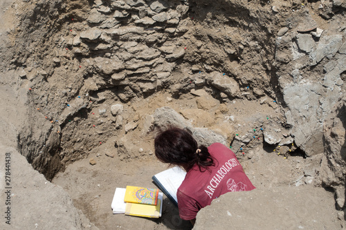 An archaeologist sits in an excavated hole making notes Canvas Print