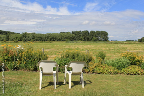 Obraz na plátně two white basic plastic camping chairs at a lawn in the garden with a beautiful