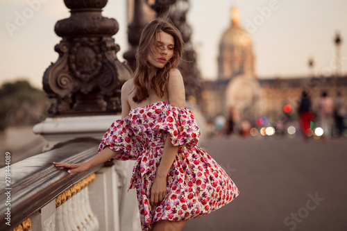 Fotografie, Obraz Beautiful girl is walking near the Eiffel tower in Paris, France
