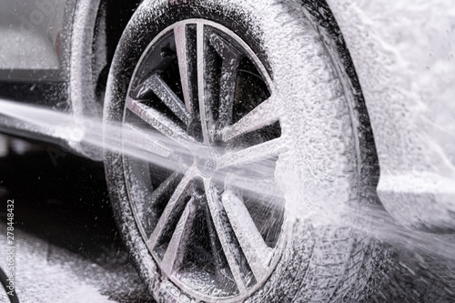 Cuadros en Lienzo Car wash worker spraying car wheel and tire with white active cleaning foam
