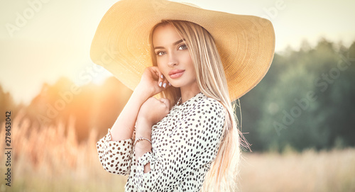 Stampa su Tela Beautiful model girl posing on a field, enjoying nature outdoors in wide brimmed straw hat