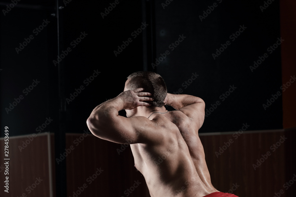Fototapety, obrazy: close up.rear view .a male bodybuilder performs an exercise