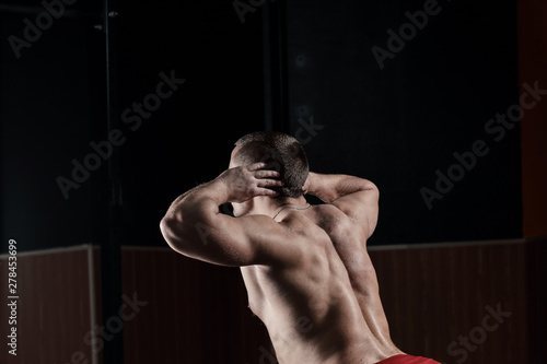 plakat close up.rear view .a male bodybuilder performs an exercise