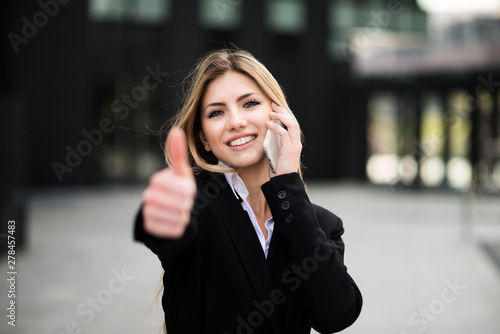 Photo Stands Akt Smiling business woman talking on the phone and thumbs up