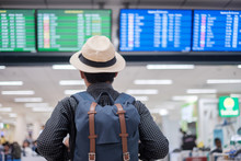 Young Man Traveler With Hat Checking Flight Time, Asian Passenger Looking To Information Board In International Airport Terminal. Travel Concept