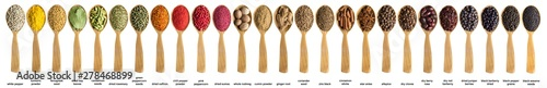 Photo sur Toile Magasin alimentation Various spices and herbs poured into a wooden spoon. Seasonings for food isolated on white background.