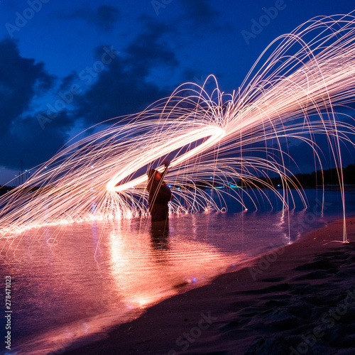 Steel wool spinning on water's edged with long exposure photography