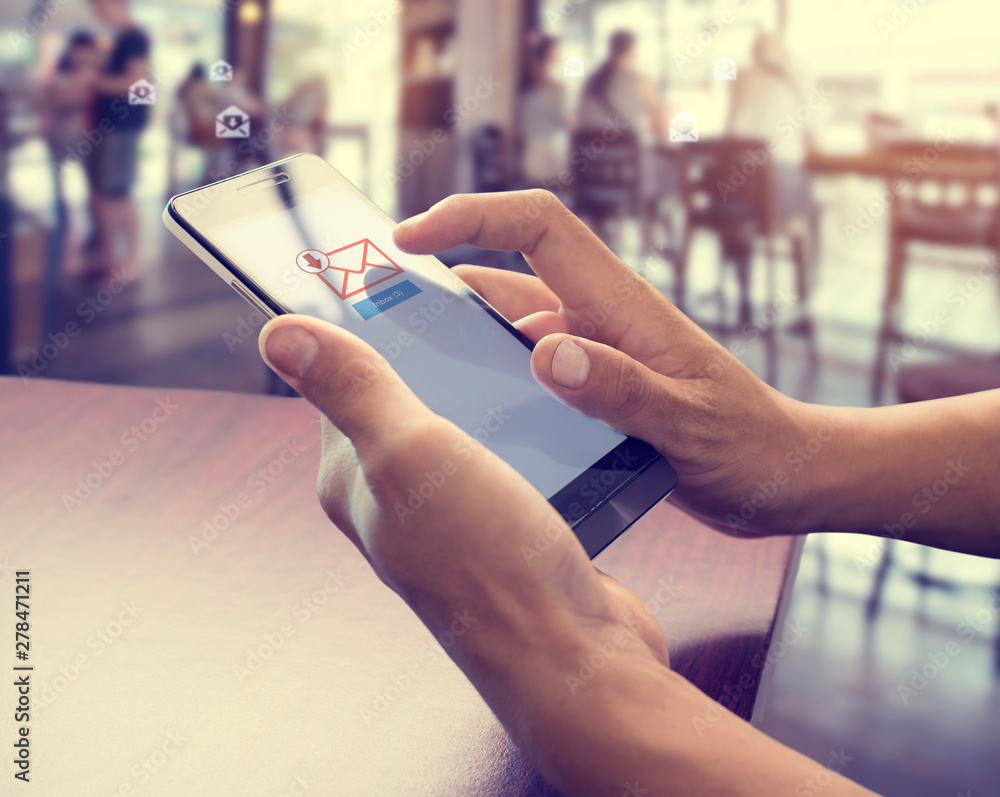 Fototapety, obrazy: Hand of male using mobile phone to open new E-mail message inbox with email symbol and envelope icon. Email marketing and newsletter concept