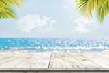 Fototapeta Kawa jest smaczna - Top of wood table with seascape and palm leaves, blur bokeh light of calm sea and sky at tropical beach background. Empty ready for your product display montage.  summer vacation background concept.