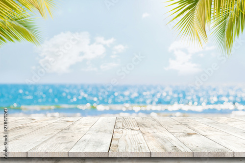 Poster de jardin Plage Top of wood table with seascape and palm leaves, blur bokeh light of calm sea and sky at tropical beach background. Empty ready for your product display montage. summer vacation background concept.