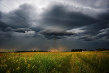 Bright Flower Field Before Of Storm, An Electric Line Pole On The Side Of A Country Road Under A Black Thunder Cloud