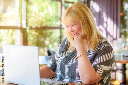Photo Portrait of busy sales plus size woman sitting in cafe and working online