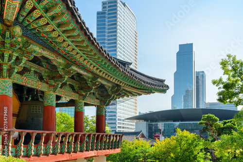 Traditional roof of Buddhist temple and modern buildings Canvas Print