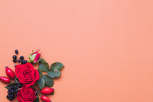 Autumn Floral Arrangement. Red And Black Fall Berries, Green Leaves And Roses On Pastel Coral Background. Copy Space.