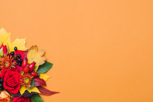 Autumn Floral Arrangement. Fall Berries, Colorful Leaves And Red Roses On Orange Background. Copy Space.