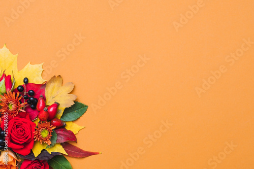 Aluminium Prints Floral Autumn floral arrangement. Fall berries, colorful leaves and red roses on orange background. Copy space.