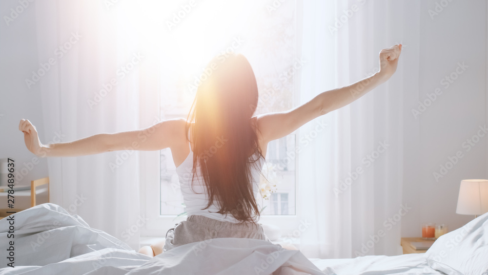 Fototapeta Beautiful Brunette is Waking up in the Morning, Stretches in the Bed, Sun Shines on Her From the Big Window. Happy Young Girl Greets New Day with Warm Sunlight Flare.