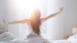 canvas print picture - Beautiful Brunette is Waking up in the Morning, Stretches in the Bed, Sun Shines on Her From the Big Window. Happy Young Girl Greets New Day with Warm Sunlight Flare.