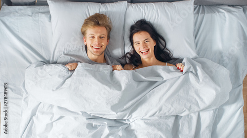 Fotografie, Obraz  Happy and Fun Young Couple Lying under Blanket on a Bed, Making Silly Faces and Laughing
