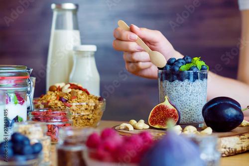 Carta da parati  Closeup female hands are preparing organic yogurt with chia for good digestion, functioning of gastrointestinal tract