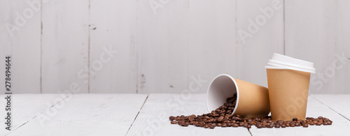 Tuinposter Cafe Paper cup of coffee and coffee beans on white wooden background