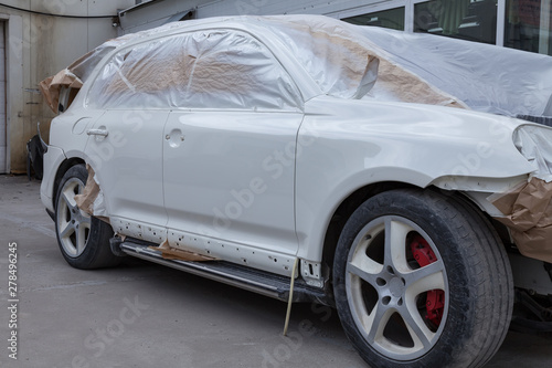 Valokuva  The car after the accident in the workshop for body repair is partially covered